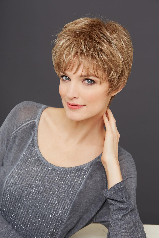 Femme qui sourie portant une perruque blond caramel