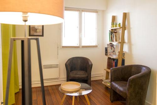 Salon Sophie Leroux comprenant chaises, lampe, fenêtre et sol parquet