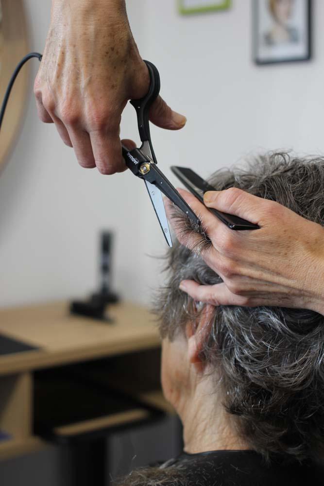 Femme senior de dos qui se fait couper les cheveux