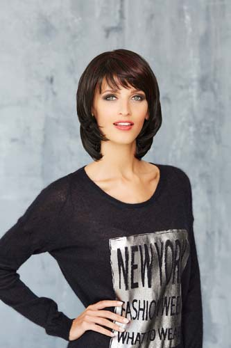 Femme qui sourie portant une perruque coupe mi-long de couleur brune