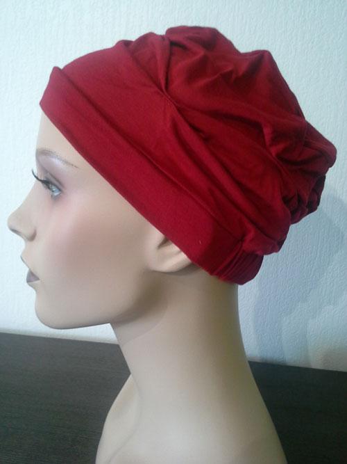 turban rouge uni posé sur une tête de mannequin