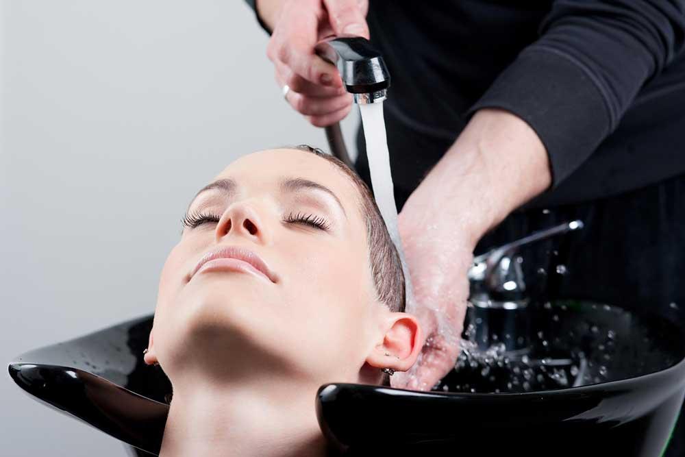 Femme se faisant faire un soin chez une coiffeuse, elle a des cheveux courts